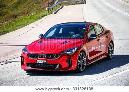 Saint Gotthard Pass, Switzerland - September 13, 2019: Red Saloon Car Kia Stinger At The Interurban