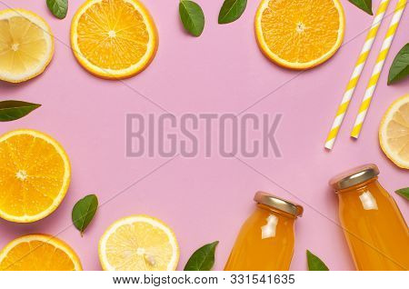Flat Lay Composition With Glass Bottles Of Juice Or Fresh, Slices Of Fresh Lemon And Orange, Green L