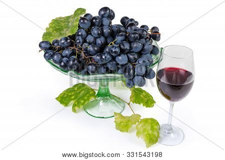 Clusters Of The Ripe Blue Grapes On The Green Glass Vintage Fruit Vase, Vine Twig With Autumn Leaves