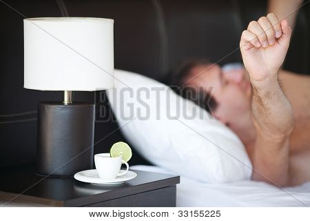 Waking Up Man And A Cup Of Tea On The Bedside Table And Lamp
