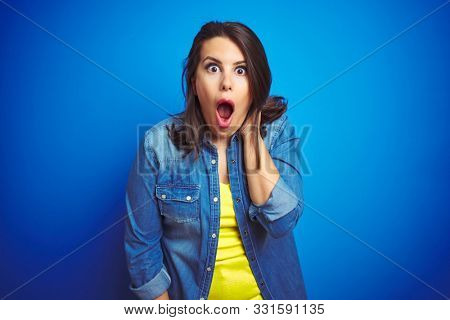 Young beautiful brunette woman wearing casual blue denim jacket over blue isolated background afraid and shocked with surprise expression, fear and excited face.