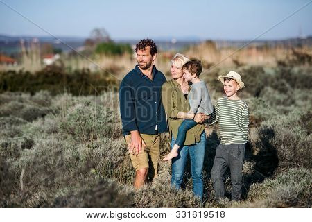 Young Family With Two Small Children Standing Outdoors In Nature.