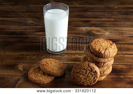 Group Of Oatmill Cookies And Milk Glass On Wooden Surface