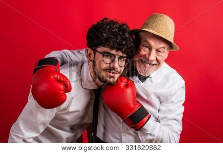 Studio Shot Of Young Versus Old Generation, A Father And Son With Boxing Glove.