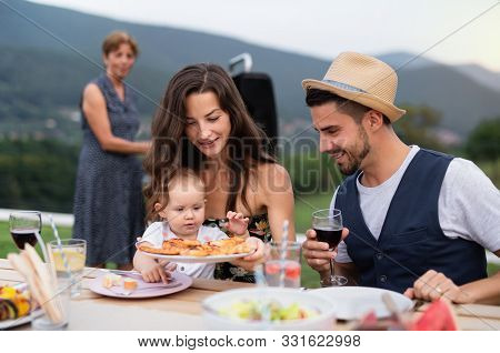 Portrait Of Family With Wine Sitting At Table Outdoors On Garden Barbecue.