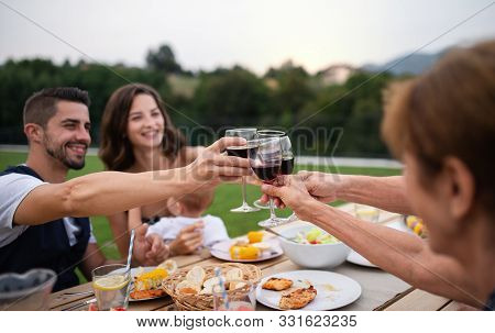 Portrait Of People With Wine Outdoors On Family Garden Barbecue.