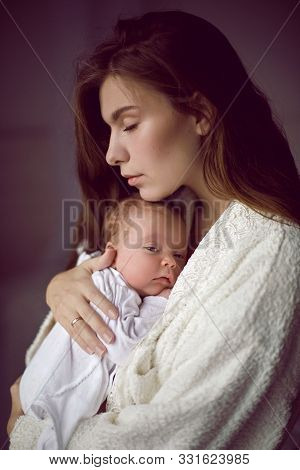 Mother In A White Robe Holds A Small Newborn Daughter Against The Wall
