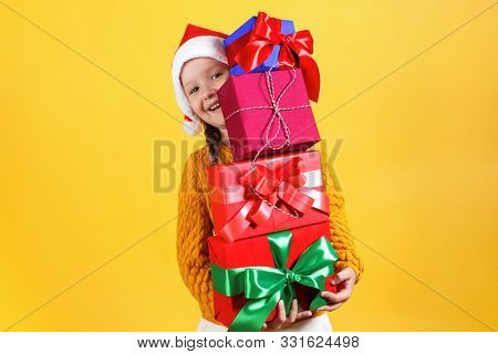 Happy Little Girl Holds A Lot Of Boxes With Christmas Gifts. Baby In Santa Claus Hat On Yellow Backg