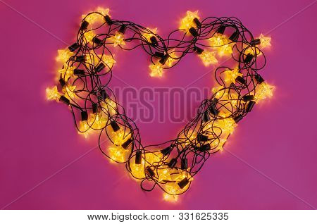 Led Garland Laid In A Heart Shape On Pink Background.