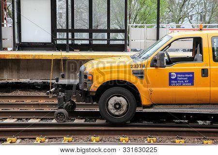 NORWALK, CT, USA - APRIL 26, 2017: Yellow Metro-North Railroad truck on railway near Norwalk station