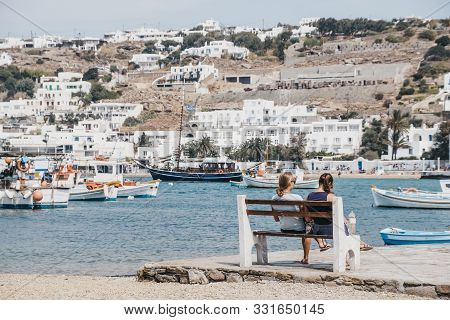 Mykonos Town, Greece - September 23, 2019: Women Relaxing On A Bench By The Water On A Sunny Day In