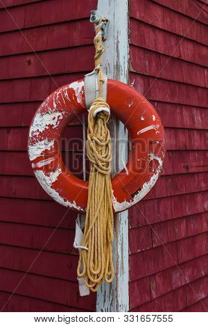 Old Red Life Preserver Ring On The Corner Of The Building, New England