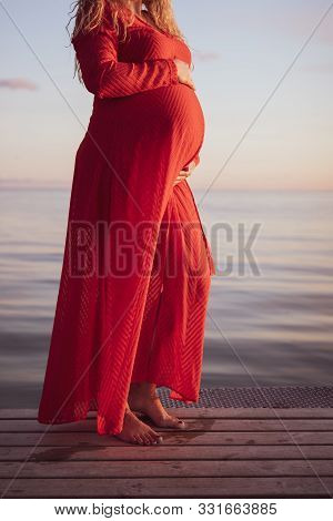 Portrait Of Beautiful Pregnant Woman In A Red Dress Touching Her Stomach, Standing Outside By The Oc