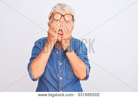 Senior grey-haired woman wearing denim shirt and glasses over isolated white background rubbing eyes for fatigue and headache, sleepy and tired expression. Vision problem