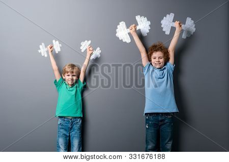 Brothers Do Morning Exercise. Two Happy Boys Standing With Raised High Arms And Holding Dumbbells De