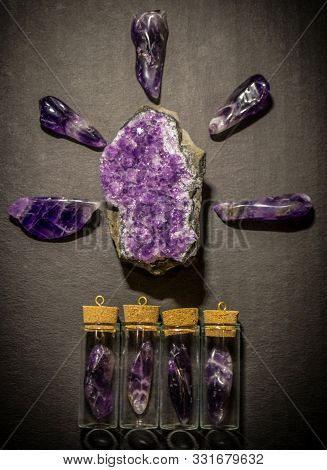 Top View On Amethysts, Amethyst Geode And Bottles With Amethysts On Dark Background