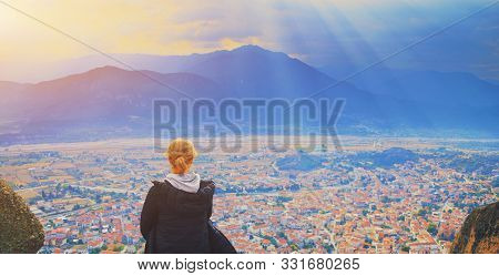 Young Woman Sitting On Top Of Cliff In Summer Mountains At Sunset And Enjoying Beautiful View Of Nat