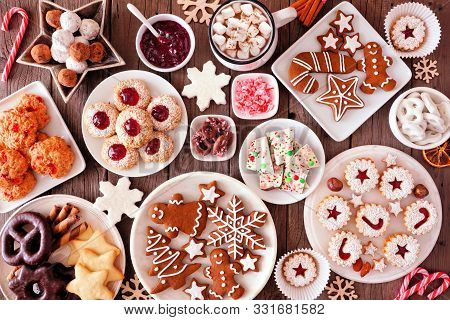 Christmas Table Scene Of Assorted Sweets And Cookies. Top View Over A Rustic Wood Background. Holida