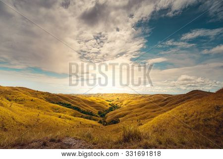 Beautiful Sunrise Climbs Sumba Island Indonesia. Scenery Nature Landscape. Amazing View on Yellow Grass Limstone Hills, Cloudy Sky and Sun. Panoramic Photo on Hilly Meadow Eco Region