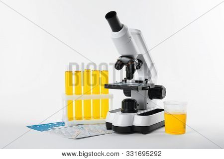 Laboratory Ware With Urine Sample For Analysis And Microscope On White Background