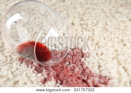 Overturned Glass And Spilled Exquisite Red Wine On Soft Carpet, Closeup. Space For Text