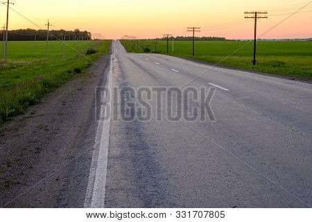 The Road Going Away In The Distance On A Summer Evening Going Over The Hills At The End Of The Road