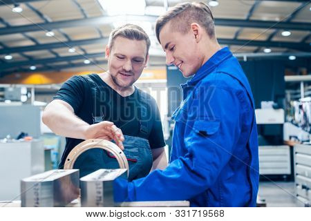 Skillful master discussing a workpiece with his apprentice or trainee