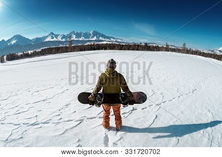 Snowboarder Stands With Snowboard Against Mountains. Backcountry Concept