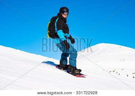 Snowboarder Riding Red Snowboard in the Mountains at Sunny Day. Snowboarding and Winter Sports