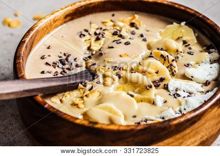 Chocolate Smoothie Bowl With Coconut Chips, Banana And Cocoa Nibs In A Wooden Bowl. Healthy Vegetari