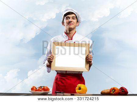 Young Male Chef Standing Near Cooking Table And Holding Blank White Board. Handsome Chef In White An