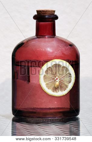 Retro Country Style Still Life With Vintage Glass Bottle And  Lemon Slice Against A High Key Backgro