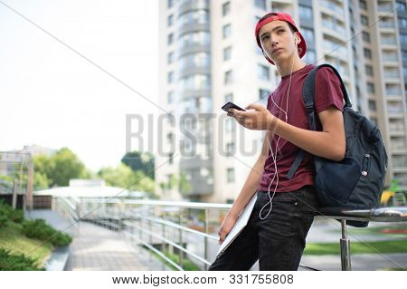 Young man  stands with backpack and holds smartphone, in the city.   Teenage boy is using mobile phone, outdoors.  Caucasian teenager in casual clothes with cell phone, urban scene.