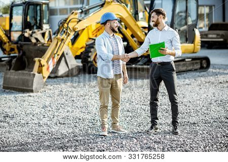 Builder Choosing Heavy Machinery For Construction With A Sales Consultant Shaking Hands On The Open