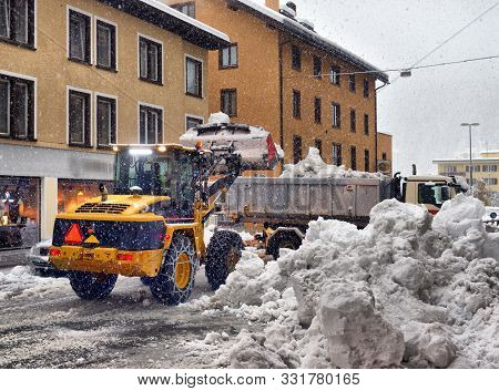Snow Cleaning Tractor Snow-removal Machine Loading Pile Of Snow On A Dump Truck. Snow Plow Outdoors