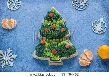 Creative Edible Christmas Tree Of Fresh Broccoli Next To Christmas Tree And Tangerines.concept: Vega