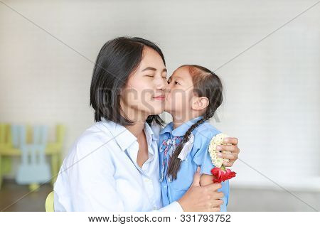 Portrait Asian Little Girl Kissing Her Mom And Hugging On Mother's Day In Thailand. Kid Pay Respect