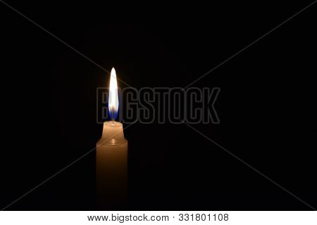Candle Burning In The Black Background. Located On The Left Side Of The Shot.