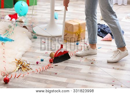 Woman Sweeping Messy Floor After Party, Closeup