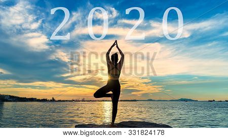 Happy New Year Card 2020. Silhouette Lifestyle Woman Yoga Near The Beach At Sunset. Healthy And Holi