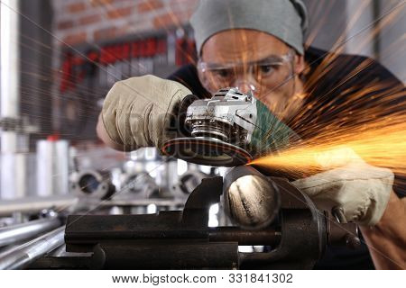 Man Work In Home Workshop Garage With Angle Grinder, Goggles And Construction Gloves, Sanding Metal