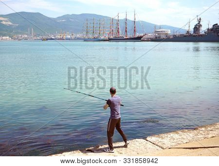 Novorossiysk, Russia - May, 2014: Fishermen with fishing rods on the pier, engaged in fishing.
