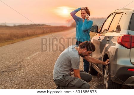 Couple Repairing Car Flat Tire On The Road In Autumn Sunset And Calling For Roadside Assistance, Sel