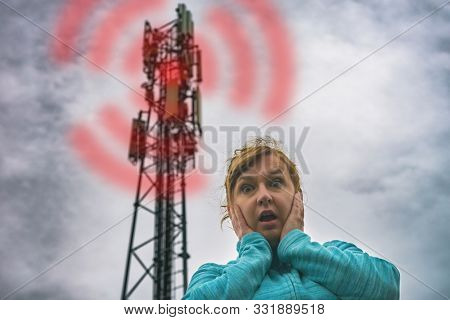 The woman is holding her head near the BTS. Harmful radiation from cellular 5G network transmitters concept