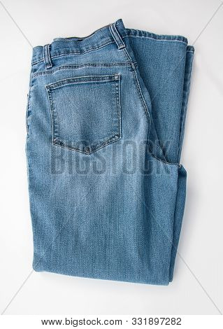 Pair Of Denim Blue Jeans Folded And Isolated On A Light Background.  A Classic Staple Of Casual Fash