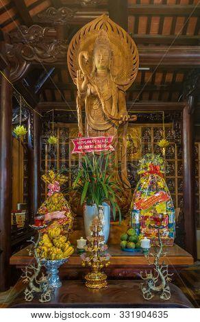 Da Nang, Vietnam - March 10, 2019: Chua An Long Chinese Buddhist Temple. Tall Light Brown Wooden Gua