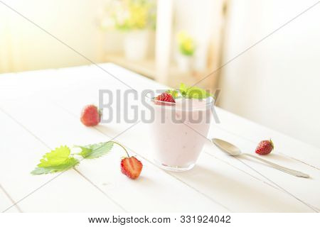 Yogurt With Strawberry In Glass On Wooden White Table In Interior