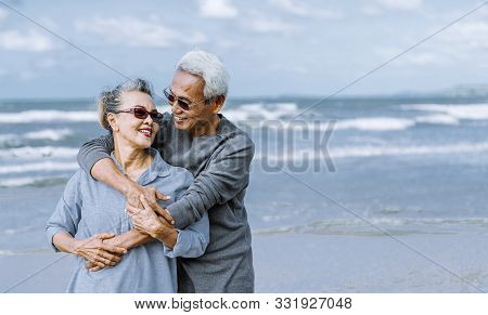 Asian Senior Couple Or Elderly People Walking And Siting At The Beach On Their Weekend Vacation Holi