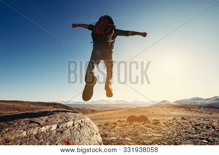 Hiker With Backpack Jumps From Big Rock Against Mountains And Sunset