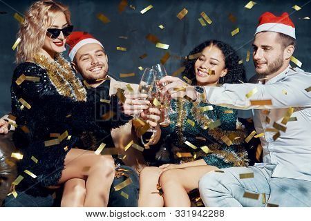Multiethnic Friends Toasting With Champagne Celebrating Christmas Or New Year, Congratulating Each O